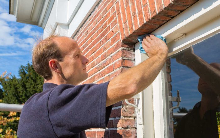 Man cleaning Vinyl Window Frames
